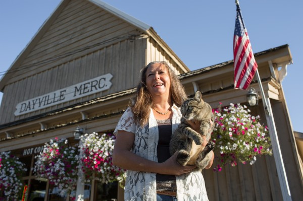 A woman and a cat standing in front of Dayville Mercantile with flowers and the American flag in the background
