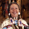 woman in traditional native american, clothing smiling at camera